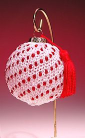 Pattern requires a glass ornament ball and 4mm beads in addition to yarn and needles.Made with Gold Rush by Plymouth Yarn