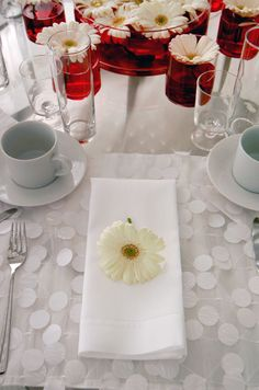 A single fresh gerbera daisy rests on a napkin at each guest's place setting.