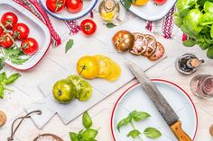 Colorful sliced tomatoes with knife by VICUSCHKA on @creativemarket