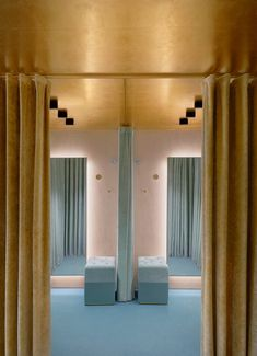 """Designed to feel """"as intimate as a boudoir"""", the dressing rooms are concealed behind heavy velvet curtains that are gold on one side and a rich shade of teal on the other."""
