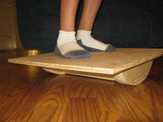 HOMEMADE BALANCE BOARD TUTORIAL-A balance/wobble board is a good way to improve balance, as well as stretch and strengthen ankles. It's also a great and fun way for small kids to develop their motor skills.