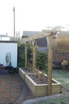 Timber raised beds with a single pergola above | Growth from the planted Wisteria and 2 different varieties of Clematis will create a green privacy screen #gardening #screens #privacy
