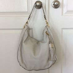 """Michael Michael Kors tasseled hobo bag Michael Michael Kors tasseled hobo bag. Buttery soft leather. Gold toned hardware. This bag is Preloved as it does have some scratches and scuffs. I think they show up more due to the light color. No tears or stains inside the bag but there are a couple of pen marks. 4 interior slip pockets, one zip pocket. Magnetic snap closure. Measures approx 14 1/2"""" l  x 13"""" h x 4 1/2"""" w. Still has lots of life left! MICHAEL Michael Kors Bags Hobos"""