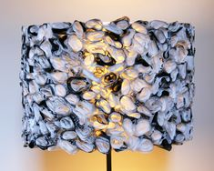 This cool lampshade is created from hundreds of black and white plastic bag rosettes. The bags are cut into long strips, rolled loosely into rosette shapes, then glued to the shade - - Ruffled Black and White Drum Shade Plastic Bag Crafts, Recycled Plastic Bags, Plastic Grocery Bags, Plastic Recycling, Recycled Lamp, White Lamp Shade, Plastic Spoons, Fused Plastic, Drum Shade