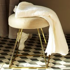 Close up of our Giza Stool, shown in polished brass with natural linen upholstery. Image from Martha Stewart Living.
