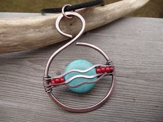 Pretty solid copper pendant necklace -Round circle in shape -Wire wrapped in a unique southwest design with turquoise howlite stone and red glass beads. -Turquoise and red is a classic combination in complementary colors. Size: Fairly large at 2.25 inches long and just under 1.75