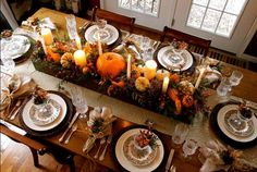 If you're worried about overdoing your Thanksgiving table decor, use a long box to help keep it contained. Here, blogger Anita Diaz filled her pallet wood box with floral foam, and then placed pumpkins, berries, candles, and cedar on top.  See more at Far Above Rubies.   - CountryLiving.com