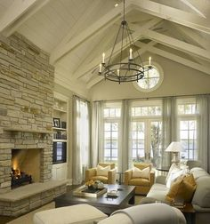 Beautiful color combo with light ceiling, stone fireplace, amazing chandelier, sheer drapery, light and medium furniture, large coffee table