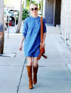 Kate Bosworth wears a denim mini dress, suede boots, a saddle bag, and cat-eye sunglasses