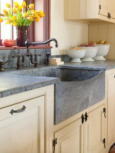 Farmhouse Kitchen - soapstone is a classic choice for a kitchen counter or sink. This farmhouse sink is backed by a soapstone backsplash that is carved in a beadboard pattern.