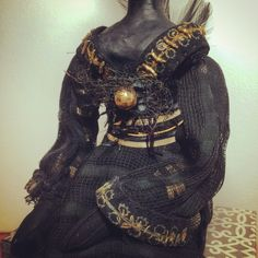 Detail of Black Beauty rabbit art doll. Made from vintage black suede gloves with gold wire trim and button, black gauze scarf, 1950's vintage hat feathers, beads, black roots from a fallentree, ribbon, hemp twine, paper cl…