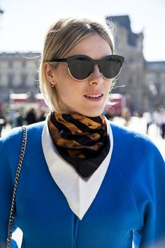 We've already mentioned how much we adore the neck scarf trend and when we saw that these scarves were being layered as we see here, we fell even more in love with the versatile accessory. This babe is looking ultra cool in her Dior sunglasses, delicate earrings, layered neck scarves worn bandana style and bright blue top.
