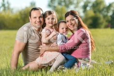 Portrait of smiling family relaxing in grass during spring day. royalty-free stock photo