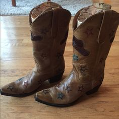 Old Gringo Cowgirl Boots Style: Abby Rose, width: B. Light tan boots with blue, turquoise & dark purple stars. The front of the boot has a small matching cow boy hat on them. As you can see in the picture the left boot has a small scuff on the tip but other then that the boots are in great shape. From heel to top the boots are a little over 13 inches. The boots come with the box as well. Old Gringo Shoes