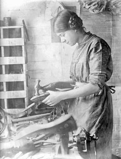 History in Photos: World War I - women workers. A woman makes and repairs shoes