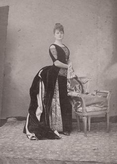 Lady in a fabulous bustle gown. France. Late 1880s.