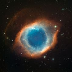 This colour-composite image of the Helix Nebula (NGC 7293) was created from images obtained using the the Wide Field Imager (WFI), an astronomical camera attached to the 2.2-metre Max-Planck Society/ESO telescope at the La Silla observatory in Chile. The blue-green glow in the centre of the Helix comes from oxygen atoms shining under effects of the intense ultraviolet radiation of the 120 000 degree Celsius central star and the hot gas. Further out from the star and beyond the ring of knots…