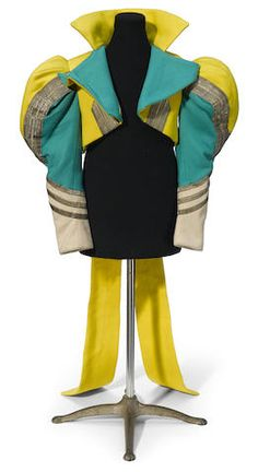 A Munchkin soldier's jacket from The Wizard of Oz (1939). Green, yellow and beige felt jacket with puffed sleeves, woven metal trim, and tails