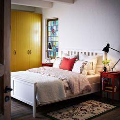 HEMNES/ヘムネス ホワイトステインのベッドにレッドのベッドサイドテーブルと、ÅKERKULLA/オーケルクラ フラワー柄の掛け布団カバー&枕カバー