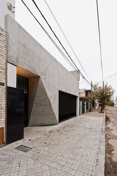 Faceted concrete T-shape facade fronts courtyard house in Santa Fe.