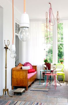 Inviting space; fun splashes of colour work so well on the white backdrop & tempered by the beautiful wooden seat