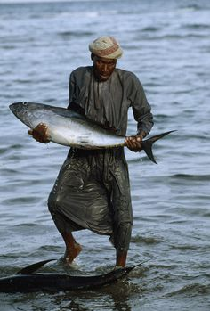A fisherman carries a tuna at the Sur morning fish market. Oman's 150 species of fish range from sardines to tuna and thirty-five species of grouper.