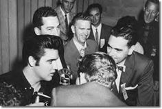 Vancouver - August 1957 - Elvis, Bruno Cimmoll, Mark Raines, RCA Rep. Ernie Henn, Tom Diskin and Norm Pringle of CDKA Radio at the Press conference in the Stadium locker room