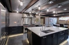 Polished concrete flooring. Under cabinet lighting along floor. Corrugated aluminum ceiling. Metal trusses. Mosaic tile backsplash/wall. Granite countertops. Stainless steel appliances.