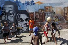 Soccer is absurdly popular in Brazil. The country hosted the 2014 World Cup, which was ironically the occasion for radical slum clearance in Brazil. Also, note that the fantasy depicted in the mural is of—another favela where kids are playing soccer, but with a slightly higher-quality ball. Source: Reuters