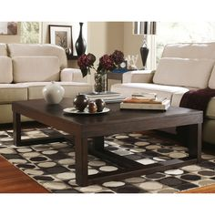 Add this contemporary cocktail table from Ashley Furniture to your home. This table features a sleek dark brown finish with its huge rectangular design this table is sure to impress.
