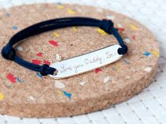 A personalised sterling silver identity bracelet on a coloured braid. The perfect gift for a trendy daddy this Father's Day.  Due to its fully adjustable design, this smart men's bracelet would be suitable for both men and boys. It has a good weighty feel and once engraved, could become an enduring record of a special event or time in someone's life. All the engraving is undertaken by Merci Maman by hand, using a French cursive style of writing. Your order will be presented to you in Merci…