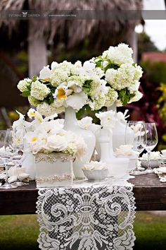Outdoor reception with farm tables, lace, milk glass and frilly white florals.  Flowers by Karen Tran.