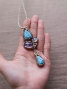 ラリマー(ドミニカ共和国産)&アメジスト(ブラジル産)&レインボームーンストーン(インド産)、マクラメ編みペンダントの紹介&販売。様々な天然石を贅沢にあしらったアシンメトリーペンダント。 ペンダント上下には、3大ヒーリングストーンの中でも癒しの力が強いとされている美しい水面模様のラリマー、 中部には、力強い輝きが印象的な、高品質レインボームーンストーンと、 山形のシルエットが見られるファントムアメジストをあしらいました。 一つのペンダントの中にいくつもの天然石をあしらった、贅沢なデザインペンダントに仕上がっています。