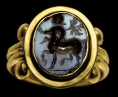 A ROMAN AGATE RING STONE.CIRCA 2ND CENTURY A.D. The flat oval stone engraved with a Centaur shouldering a branch, on a short groundline; mounted as a ring in a modern gold setting
