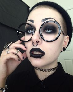Love her eye makeup. Love those humongous round glasses. Love her black lipstick. Love her eyebrows. Love!! Goth