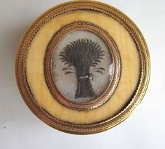 "A very fine English Georgian Era snuff box made of bone, gold, woven hair, glass, and tortoiseshell snuff box, with a Guilloché gold border. The central panel is inset with hair woven in a ""sheaf of wheat"" representing the season of Autumn, a time described by English poet John Keats' as one of mellow fruitfulness. Rare and in immaculate condition. Hallmarked, but illegibly."