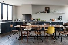 Eat in kitchen and dining room - dark lower cabinets + mixed vintage chairs // Chabrol Apartment by Antonio Virga   HomeAdore