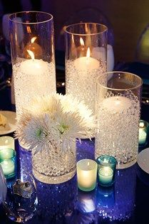 Votive candles are placed atop a sea of clear gems in glass hurricanes while blue candle holders are illuminated by tealights.