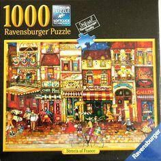"Amazon.com: Ravensburger Puzzle ""Streets of France"" Art by Jennifer Garant 1000 Piece Jigsaw Puzzle Premium Softclick Technology Pieces: Toys & Games"