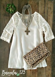 Perfect essential top in Off-White featuring crochet 3/4 sleeves. V-neck with…