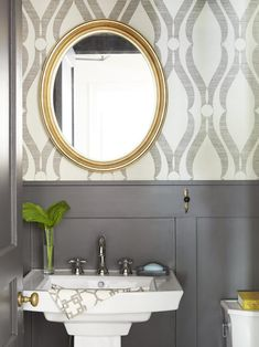 """Printed grass cloth wallpaper and brownish-black painted wainscoting (Black Fox by Sherwin-Williams) are a sophisticated duo in the bath. """"It's a bold pattern in a small room,"""" says Ceri. """"But it works because the colors are muted."""""""