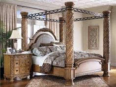 Bedroom: Gorgeous Cherry Wood Canopy Bed With Wrought Iron Top And Carved Wood Crown Molding Varnished Wooden Bedroom Vanity Cabinet With Mirror Traditional Area Rug Over Concrete Wood Floor from Wooden Canopy Bed for Tropical Vacation