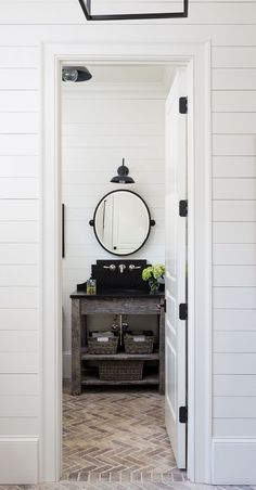 Farmhouse powder room. They used weathered wood for the console and leathered black pearl granite for the countertop and backsplash. Light fixture is RH. The brick in the herringbone pattern adds interest.