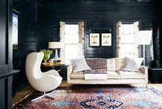 Cozy sitting room with black paneled walls, white upholstered furniture, and a bright Persian rug