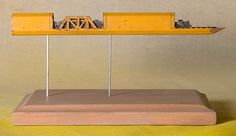 """This recent piece by Nebraska-based artist Cindy Chinn is particularly ingenious, an entire carpenter's pencil is turned into a tiny train, trestle, & bridge. """"This piece was designed using straight lead pieces for the rails, with the tiny carved train placed and securely glued on top of the rails,"""" Chinn shares. """"The train engine is only 3/16″ of an inch tall. The pencil is 5-5/8″ long & mounted in a wood shadowbox frame as shown in the photos."""""""