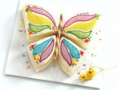 Cut the cake in half, and then cut each half into ⅓ and ⅔ pieces. Arrange the pieces so that the curved sides meet at the center to form the wings. Use a colorful candy stick for the body, and decorate with colored frosting, sprinkles and candies.