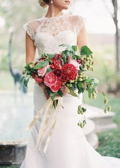A bouquet with raspberry-hued garden roses, dahlias, and ranunculuses, with fresh greenery and elegant trails of hops cascading down the side | Brides.com