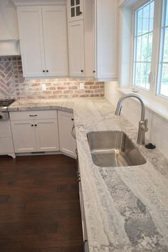 Amazing kitchen features a white shaker cabinets paired with gray quartzite countertops fitted with a curved stainless steel sink and a white subway tiled backsplash.