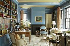 A Greek key–patterned Tibetan rug in Garrow Kedigian's library creates a neutral contrast to the blue-lacquered walls.