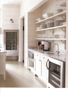 I love the simplicity of this kitchen from Atlanta Homes Magazine...so clean and fresh with everything you need at your fingertips. Notice the library light accenting the glass front refrigerator {maybe not a good idea at my house!}
